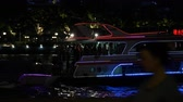 YIWU, CHINA - MAY 2018: Asia illuminated panorama of beautiful night city in blue blinking lights. Touristic and business center. Seaside, ruising ship with people moving on the river reflecting