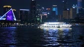YIWU, CHINA - MAY 2018: Asia illuminated panorama of beautiful night city in blue blinking lights. Seaside, ruising ship on the river reflecting in the water, enjoyment concept