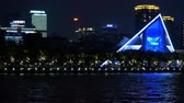 YIWU, CHINA - MAY 2018: Illuminated panorama of night city in timelapse. Beautiful asian modern style of buldings and development of constructing, Blue lights blinking and reflecting in the river