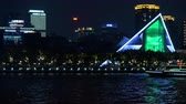 YIWU, CHINA - MAY 2018: Urban scene: illuminated panorama of dark night asian city. River side and modern in blue lights. Cruising ship moving on the river. High buildings reflecting in the water Stock Footage