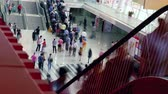 YIWU, CHINA - MAY 2018: People spending time in the big shopping center, moving on escalators and walking. Airport arrival terminal, check in point and shops. Travelers waiting for the flight