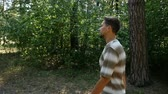 finom : A tall young man with a sportive figure walks freely in a green forest on a sunny day in summer in slow motion. The forest is full of pines and maples. Stock mozgókép