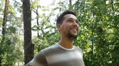 finom : A happy young bearded man smiles sincerely in a pine forest while standing in profile among high trees on a sunny day in summer in slow motion Stock mozgókép