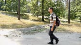 finom : A relaxed young man with a backpack walks along a footpath in a pine forest on a sunny day in summer in slow motion.  The forest looks natural and nice. Stock mozgókép