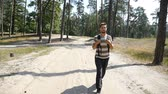 finom : A high sportive young man with a backpack goes along a sandy footpath in a pine forest on a sunny day in summer in slow motion.  The forest looks natural and pleasant.