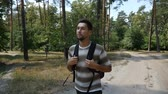 finom : A relaxed young man with a backpack goes along a footpath in a pine forest on a sunny day in summer in slow motion.  The forest looks natural and nice. Stock mozgókép