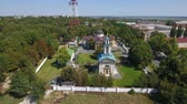 esplêndido : An exciting aerial shot of an old orthodox church from a bird`s eye perspective in summer on a sunny day. It has a blue doom a golden cross and a picturesque park around it. The skyscape is great Stock Footage
