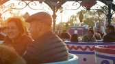 podšálek : Paris, France - November 7, 2017:An optimistic view of a roundabout and happy people riding it in Disneyland in France. The circling cups and saucers look fine at sunset in slo-mo