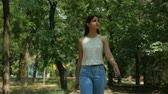 лиственный : Portrait of a happy young woman with long loose hair in  jeans and sleeveless blouse standing and smiling happily in leafy park on a sunny day in summer