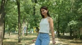 Cheery view of a beautiful brunette woman with long loose hair in a sleeveless blouse and jeans strolling in a green park with leafy trees in summer
