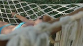 netting : Relaxing view of a stylish woman with a bob haircut in blue bikini and black sunglasses having a rest in a swinging hammock fixed among trees in slo-mo Stock Footage