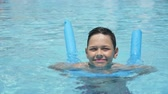 楽観 : Portrait of a smiling dark-haired boy squinting his eys and entertaining in a swimming pool with a floating rubber tube in summer in slow motion