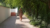 otimismo : Impressive view of an elegant blond woman in bikini and pareo walking along an alley in a hotel placed at a resort beach in summer in slo-mo