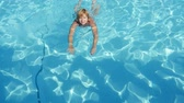 otimismo : Exciting view of a smiling blond woman in bikini swimming breastsroke to a cameraman in a light blue swimming pool outdoors in summer in slow motion Stock Footage