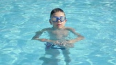 aguas frescas : Cheery view of a happy child in goggles moving down and up in a swimming pool with see-through light blue waters in summer in slow motion