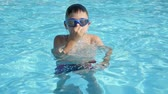 aguas frescas : Jolly view of an entertaining brunet  child in goggles moving down and up in a swimming pool with clean celeste waters in summer in slow motion