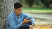 discagem : Optimistic view of a happy brunet teenager browsing the net and chatting with his darling under a big tree in a picturesque park in autumn