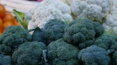 цветная капуста : Exciting macro shot of green and white cauliflower heads having dark, dotty and spheric surface. They are placed with tomatoes in market in autumn. Стоковые видеозаписи