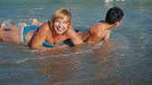 楽観 : Cheery view of a smiling blond woman and her playing jolly boy lying on their stomachs under tidying waves on sandy beach in summer in slow motion