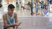 jovial : Cheery view of a young sportive man with a short haircut in a singlet and shorts sitting, smiling and browsing the net on his phone in mall Stock Footage