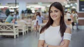gevşemiş : Optimistic view of a happy young woman with long loose hair in a fashionable white dress standing and smiling with crossed hands in a large mall Stok Video