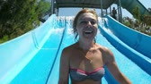 otimismo : Jolly view of a smiling blond woman in bikini riding down a steep chute and taking a selfie in a Turkish aqua park on a sunny day in summer Stock Footage