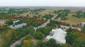 административное здание : Splendid bird`s eye view of a three storey house, green parks and a straight highway passing through a village in Kherson region in summer