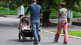 pram : RUSSIA, OREL - 31 MAY 2014: Family with twins is walking in the park Stock Footage