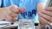 podatki : Man in blue T-shirt counting dollars and filling tax form