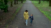 A beautiful mother and her cute little daughter walking in the park.