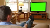 drótnélküli : 5070 A man in his living room changes the channel and watches television.  Green screen for your custom content.