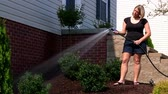 gramado : A woman waters her garden. Stock Footage
