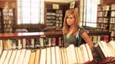 образование : A student locates a book in the library.