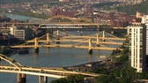 por que : The Three Sisters Bridges in Pittsburgh, PA.  They are three very similar self-anchored suspension bridges spanning the Allegheny River.These bridges are historically significant because they are the only trio of nearly identical bridges, as well as the f