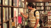 buscar : A student locates a book in the library.