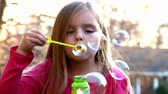 humor : A little girl blows bubbles.  Shot at 60fps. Stock Footage