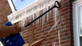 breaking : Breaking off dangerous hanging icicles from the roof.