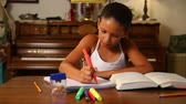 caderno : A young girl does her homework by herself in the dining room.
