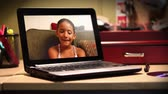 etnický : A young girl video chats on a portable laptop.