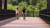 bisiklete binme : A young couple bike and sightsee on the bike trails on Washingtons Landing, an island on the Allegheny River near Pittsburgh, Pennsylvania. Stok Video