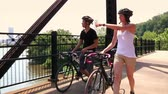 bisiklete binme : A young couple walk their bikes on a pedestrian bridge over the Allegheny River near Pittsburgh, Pennsylvania.