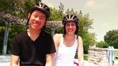 bisiklete binme : A young couple in bicycle helmets smile at the camera.  Shot at 60fps for true slow motion.