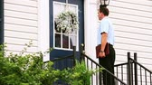 A door to door salesman walks up to a house and knocks on the door. Stock Footage