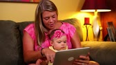 handheld : A mother uses a tablet computer with her young baby on the sofa. Stock Footage