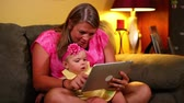 olhar : A mother uses a tablet computer with her young baby on the sofa. Stock Footage