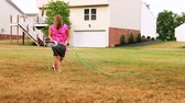 gramado : A female homeowner moves the sprinkler in her backyard. Stock Footage