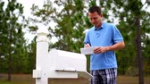stres : A worried man gets his mail outside of his house.