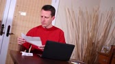 overdue : A man pays his bills on his laptop. Stock Footage