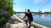 lovaglás : A man rides his bike on Pittsburghs river bank.