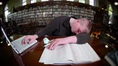 caderno : A tired male student sleeps in the library. Stock Footage